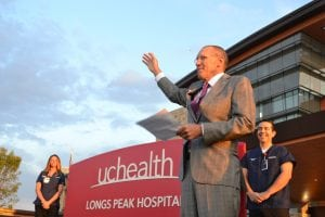 Hospital president stands in front of facility on opening day and gestures to crowd gathered.