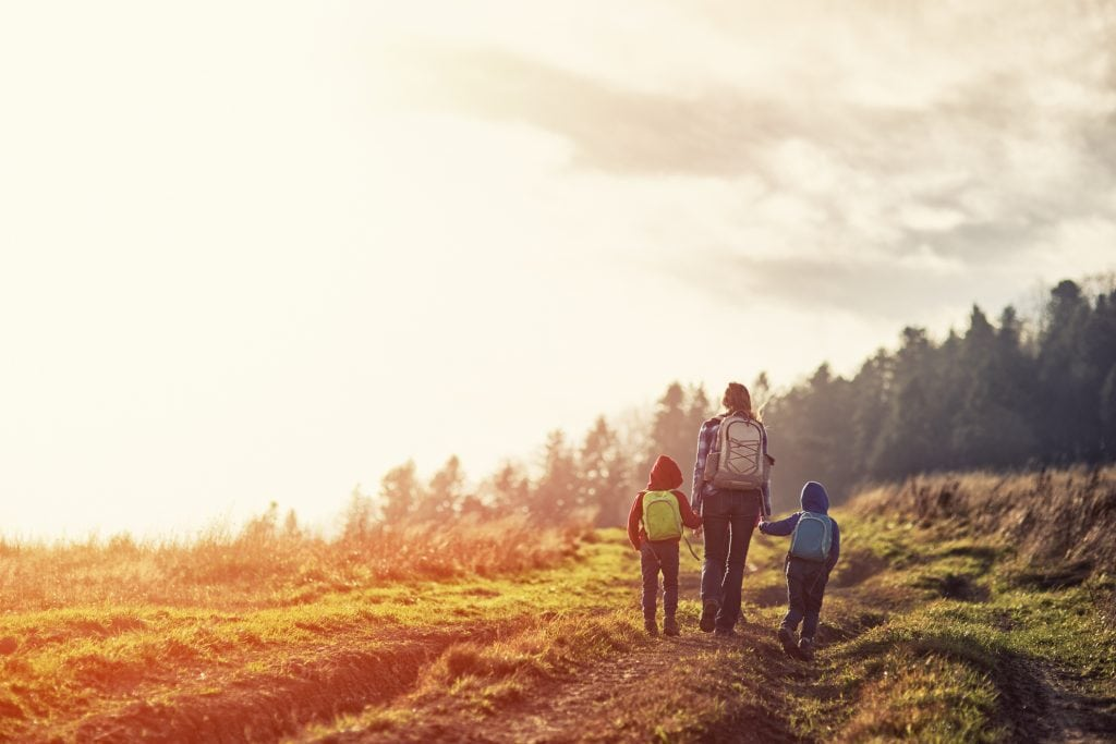 A mother and two young children are hiking during sunset.