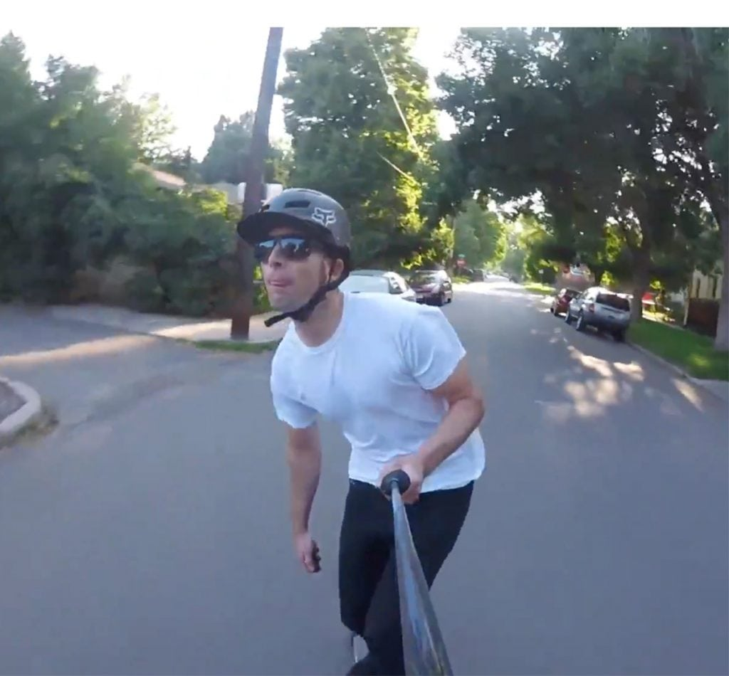 A man rides on an electric longboard while filming himself with a ski pole
