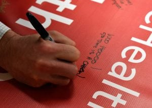 Man's hand is shown writing a congratulatory message on a banner.