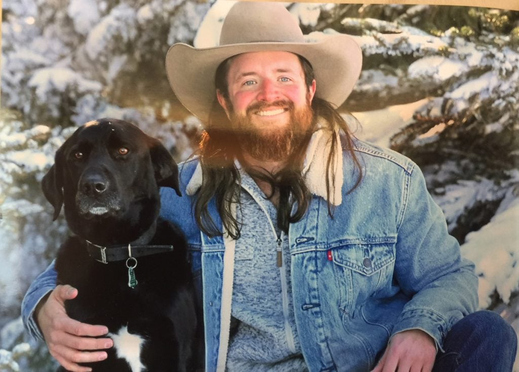 Nathan Kissack has long hair and a full beard in this photo from his Wyoming ranch. He poses with his black lab.