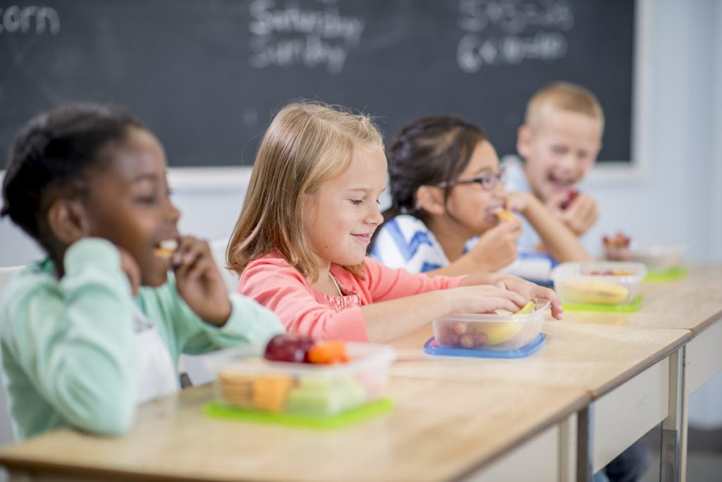 A group of children sit at their desks in a classroom eating lunch.