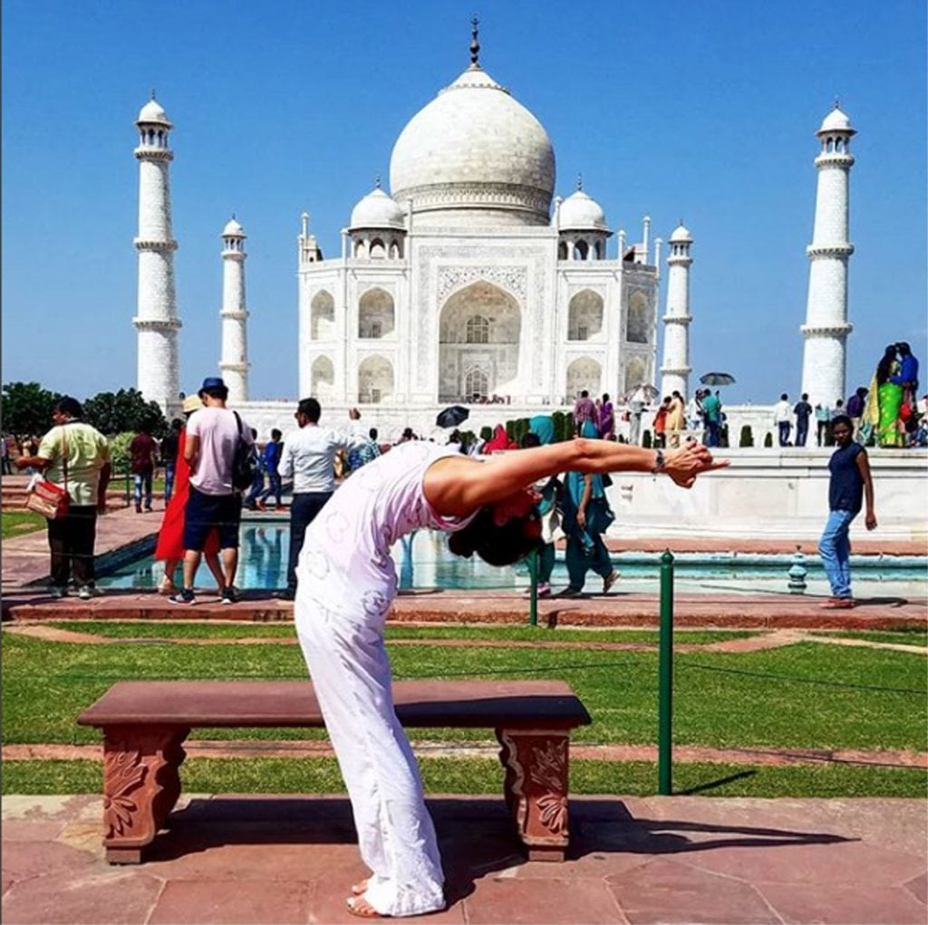 A woman wearing white does a yoga pose in front of the Taj Mahal in India.
