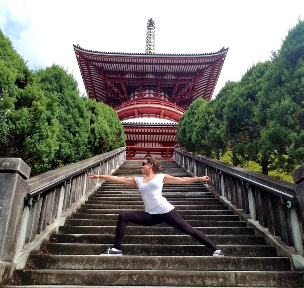 Breast cancer survivor Louisa Drouet does a yoga pose in front of a temple in Asia.