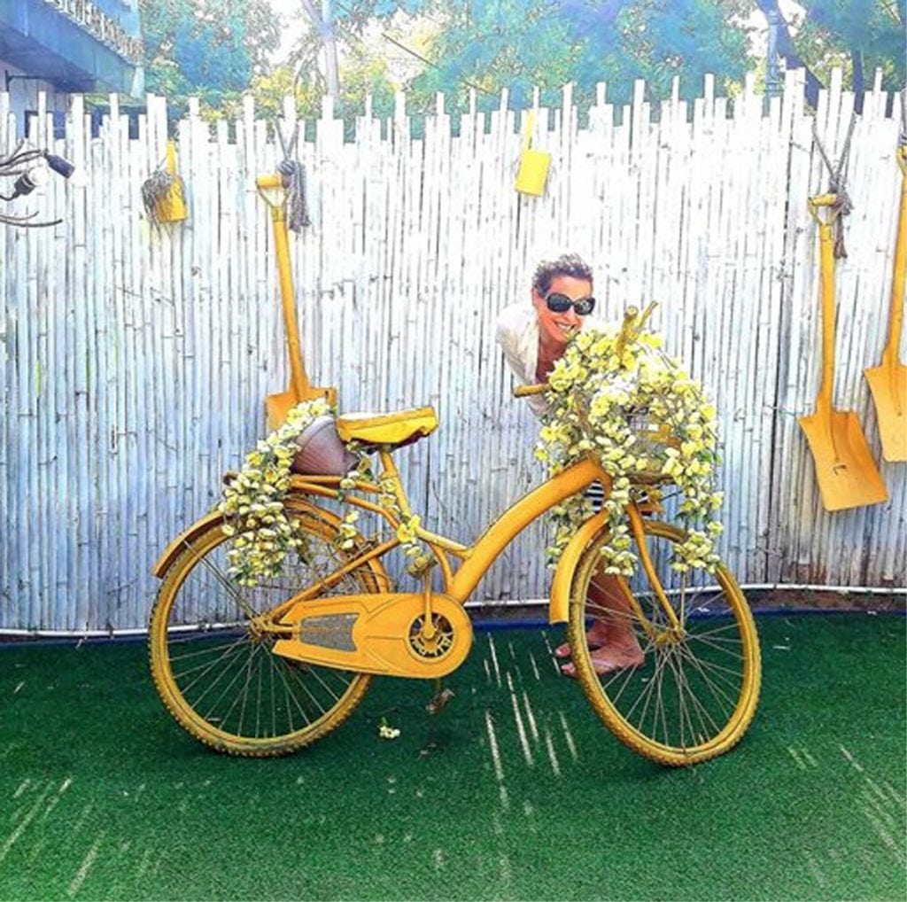 Louisa Drouet poses with a white fence, a yellow bike and other yellow items in a photo from India.