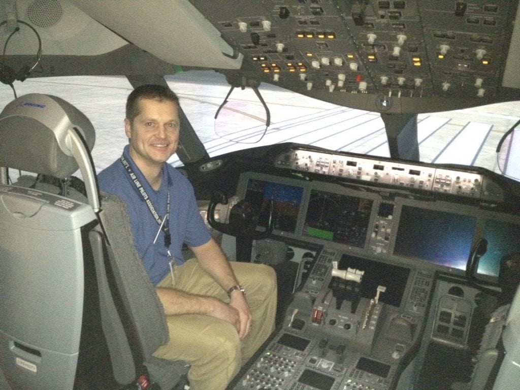Brian Malek sits in the cockpit of a Boeing 787.