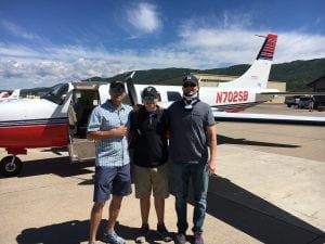 Brian Malek poses with his brother-in-law and nephew in front of an airplane.
