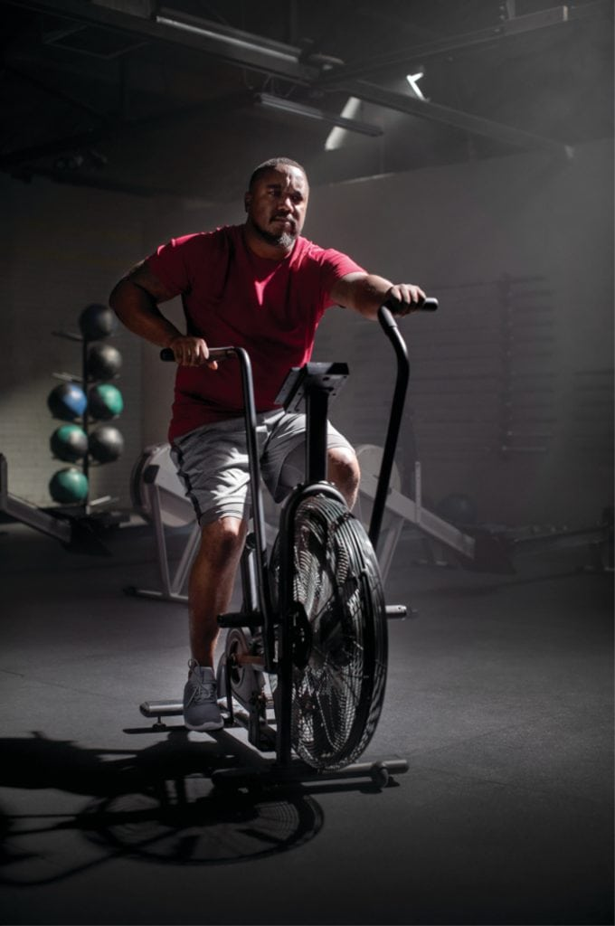 David Kenyatta riding an exercise bike after recovering from a stroke.
