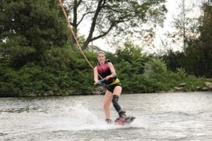 A woman wakeboards. Her left leg is amputated and she wears a prosthetic.