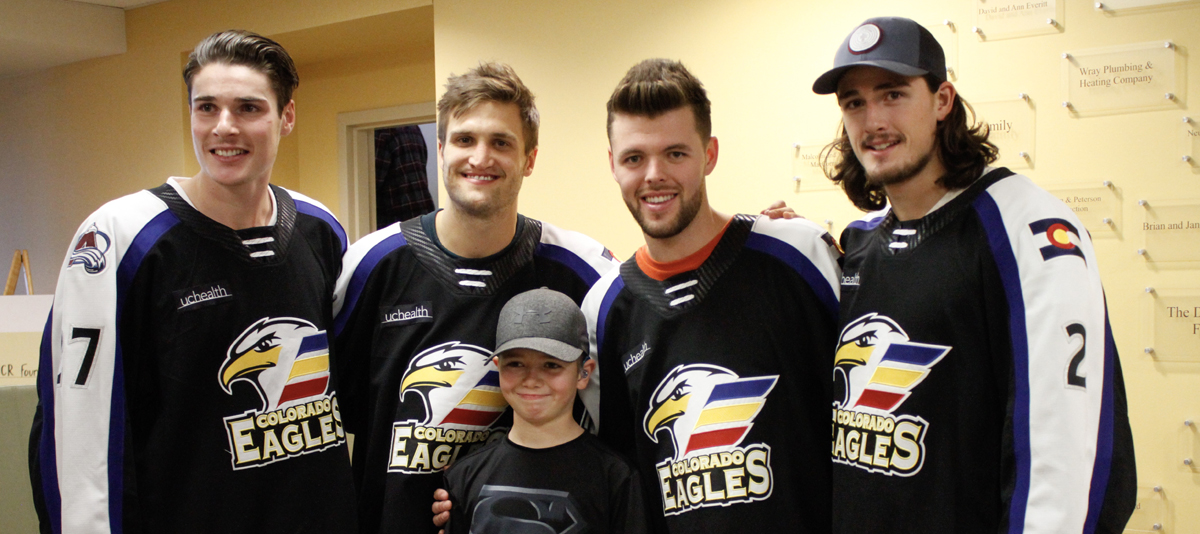 four colorado eagle players lined up with boy in front