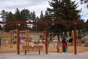 Memorial Park in Woodland Park. The playgound is in the foreground. There are pine trees in the background.