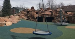 A playground in Boulder features new play equipment in the foreground and a red rock structure in the background.