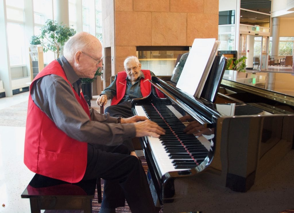 Two older men in red volunteer vests perform at UCHealth University of Colorado Hospital. One is 81 and is playing the piano in the foreground. The other is a 94-year-old WW II vet. He's in the backgrounda and is smiling before he sings.