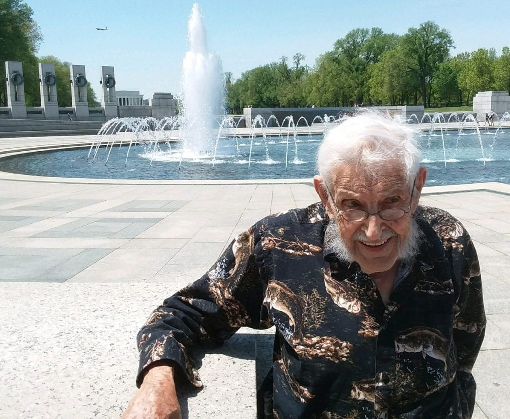 94-year-old WW II veteran Virgil Hughes stands in front of a fountain at the WW II Memorial in Washington, D.C.