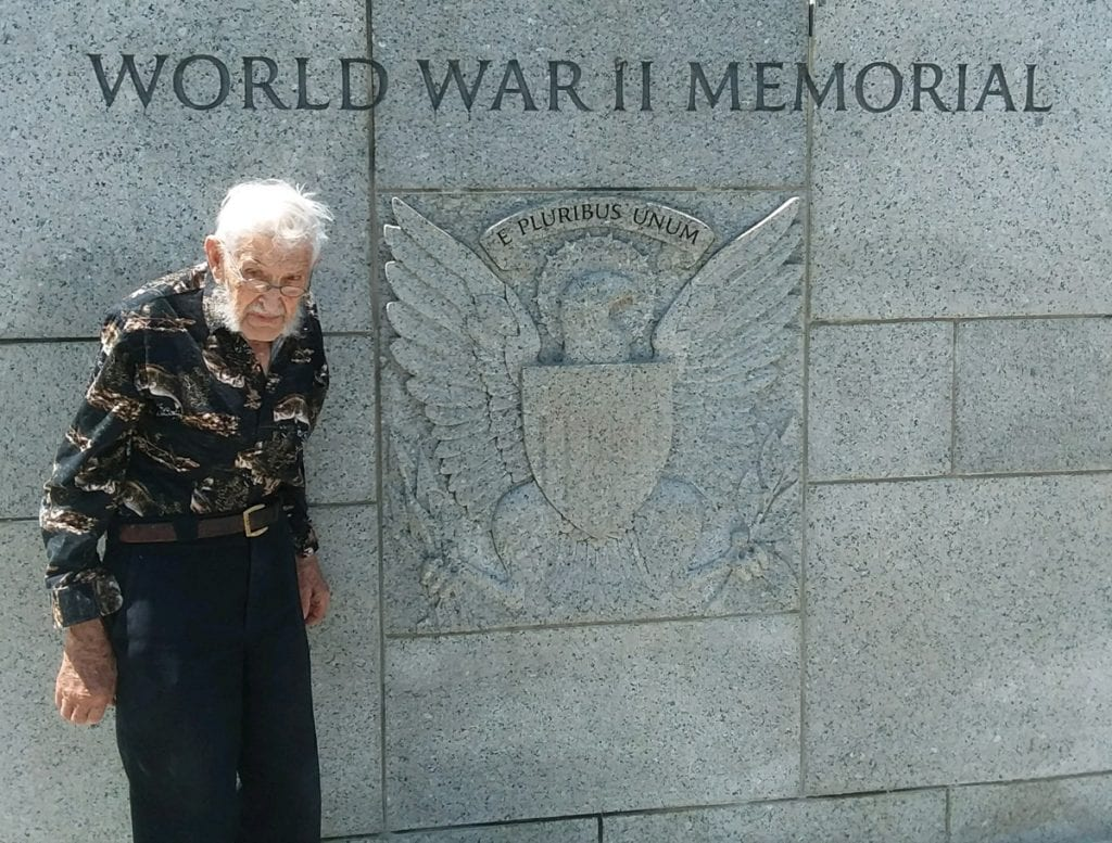 A 94-year-old WW II veteran, Virgil Hughes, poses with a sign that says World War II Memorial. He visited the memorial in Washington, D.C. in May.