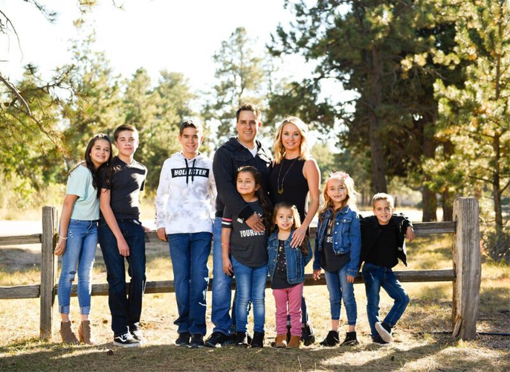The Cuellar family poses for a photo at Black Forest Regional Park: (From L to R) Samantha, 17; Aiden, 13; Michael, 14; Randy; Grace, 9; Shelly; Victoria, 3 ½; Isabella, 7; and Jeremiah, 5.