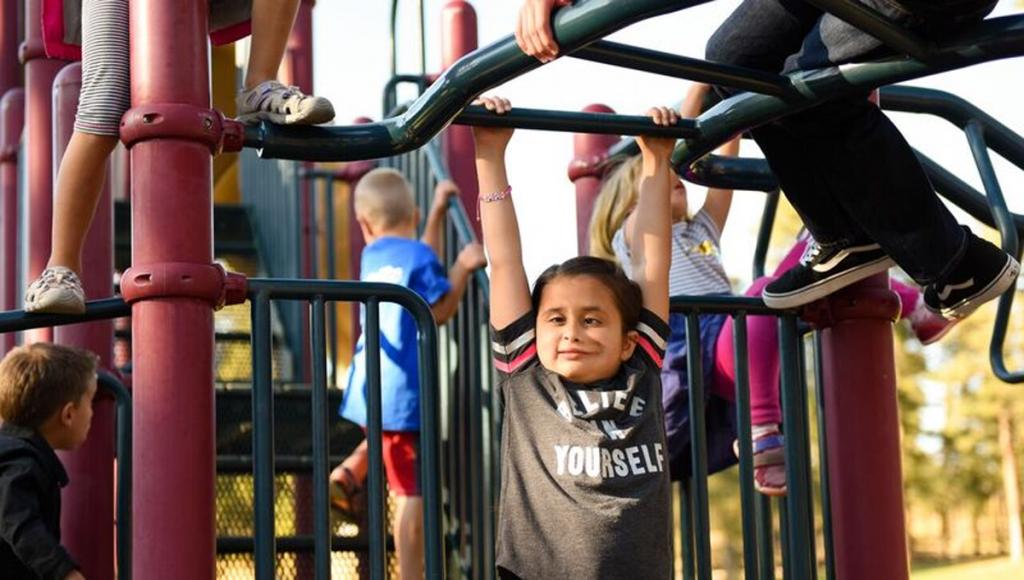 Grace Cuellar swinging from playground equipment.