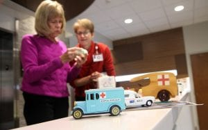 Kathy holds a toy ambulance while Joann looks at it.