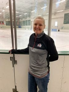 Mary standing in front of a hockey rink