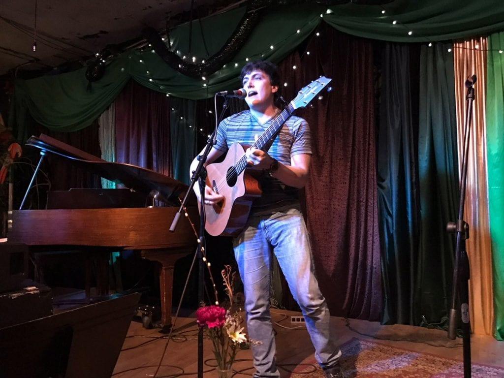 Daniel Schwartz playing guitar during an open mike night.
