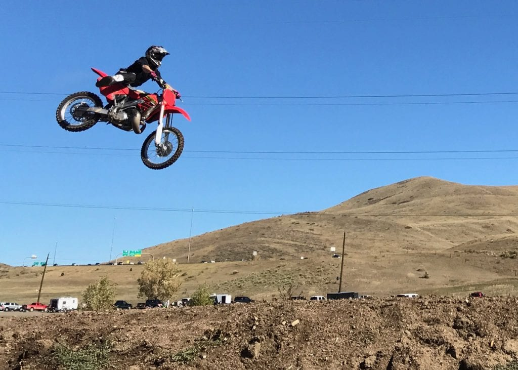 Eric Rice rides a motocross bike and flies over a dirt mound.