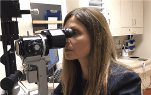 Pelak looks through eye exam equipment.