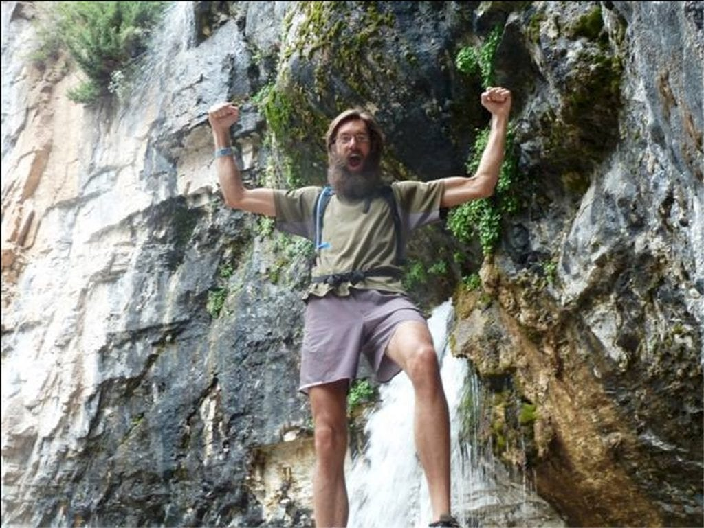 Andy Bonnett holds his arms up while hiking. A waterfall is in the background.