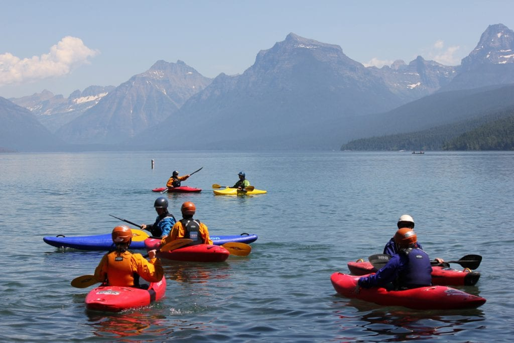 Kayakers in red and yellow kayaks paddle on a lake in Montana with the peaks of Glacier National Park in the backround.
