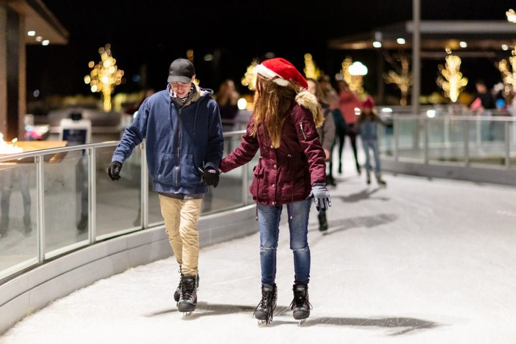 A young couple holds hands and skates at the Parker Ice Trail in Discovery Park.