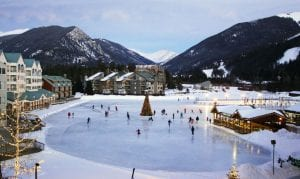 Skaters on a pond at Keystone with snow-covered mountains in the background.
