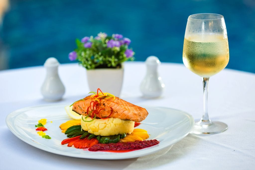 a photo of salmon with white wine in the background