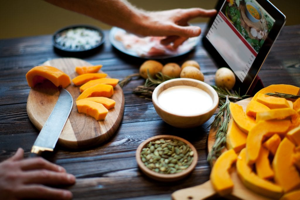 A recipe is on a tablet as a person chops vegetables.