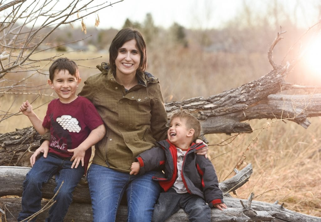 A mom sits on a log and poses with her two young sons, ages 4 and 2. Both kids are laughing and the younger one is looking up at his mom.