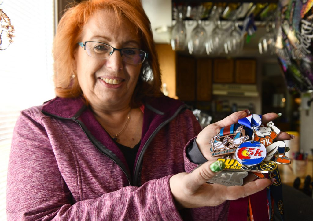 "Linda Chandler shows off some medals she has received from walks and runs. Signing up for events keeps her motivated to move. She loves the ""bling"" and has lost 70 pounds since May. Photo by Cyrus McCrimmon for UCHealth."
