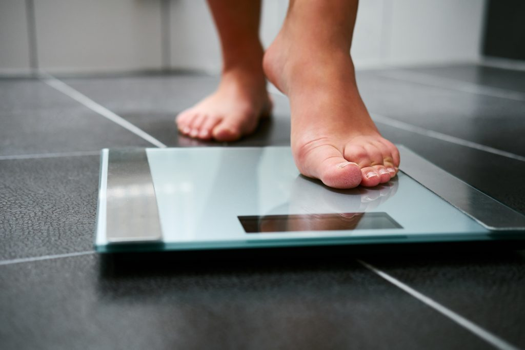 A woman with barefeet stepping on a scale.