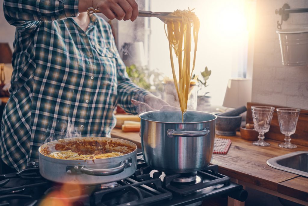 A photo of a woman pulling pasta from a pot of boiling water.
