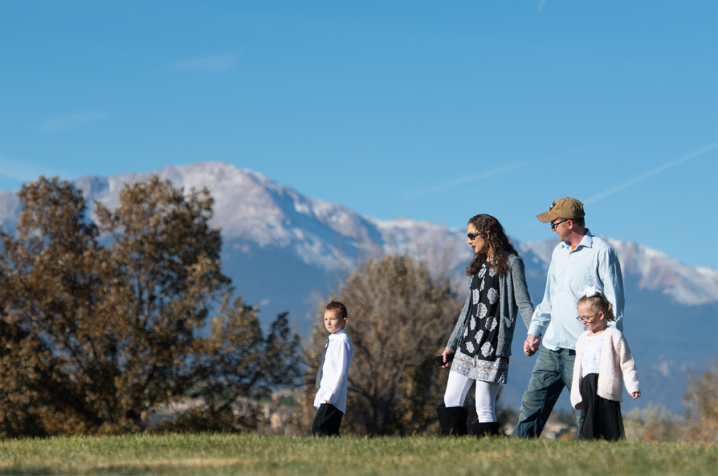 The Wickman family goes for a stroll in a park near their home in Colorado Springs. Pikes Peak is in the background.