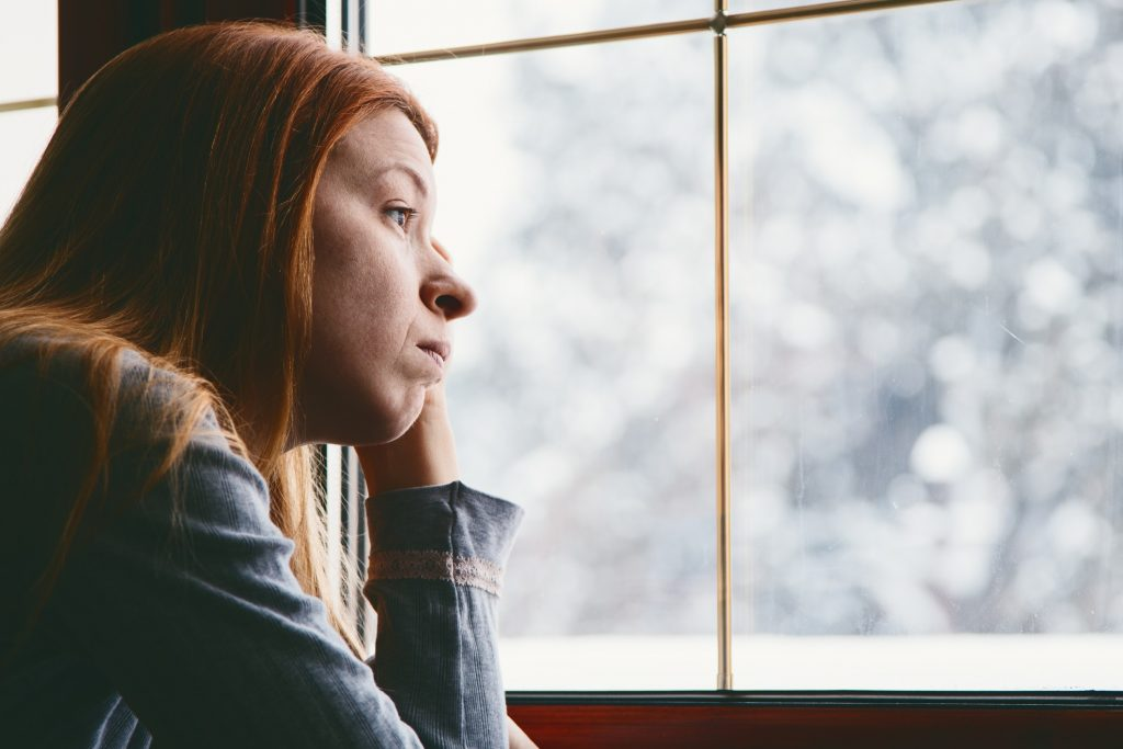 A sad woman looks out the window on a winter day.