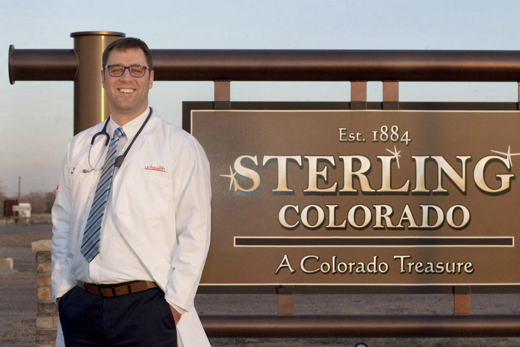 Dr. Daniel Lambrecht stands in front of a sign welcoming people to Sterling, Colorado