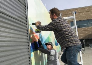 Two men install one of 55 art panels that now cover an air handler on the roof of UCHealth Longs Peak Hospital.