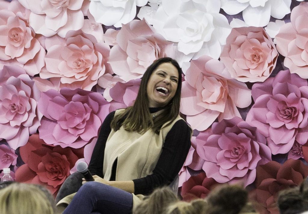 Softball Olympian Jessica Mendoza smiles with a floral background during evre, a UCHealth women's health event.
