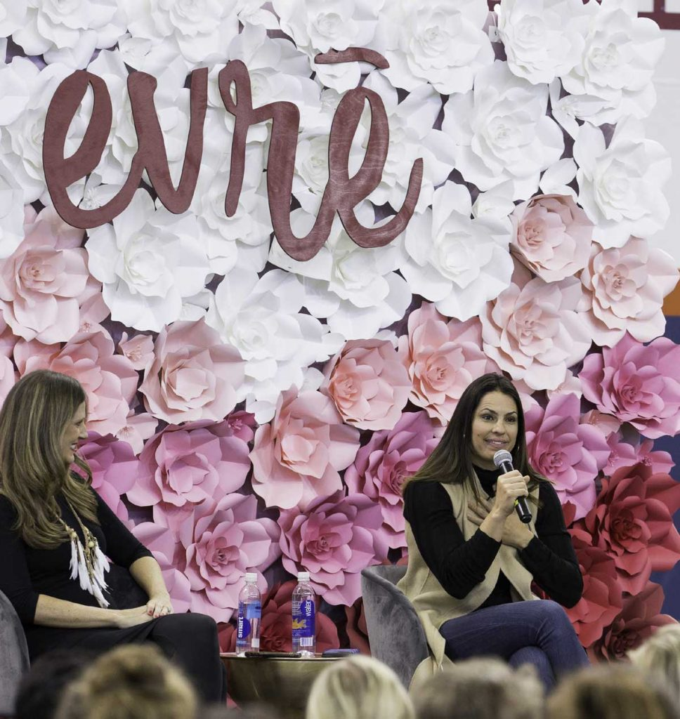 two women speak during UCHealth's womens health event called evrē. They are in front of a floral background. To the left is social media pioneer, Amy Jo Martin. To the right is ESPN baseball commentator, Jessica Mendoza.
