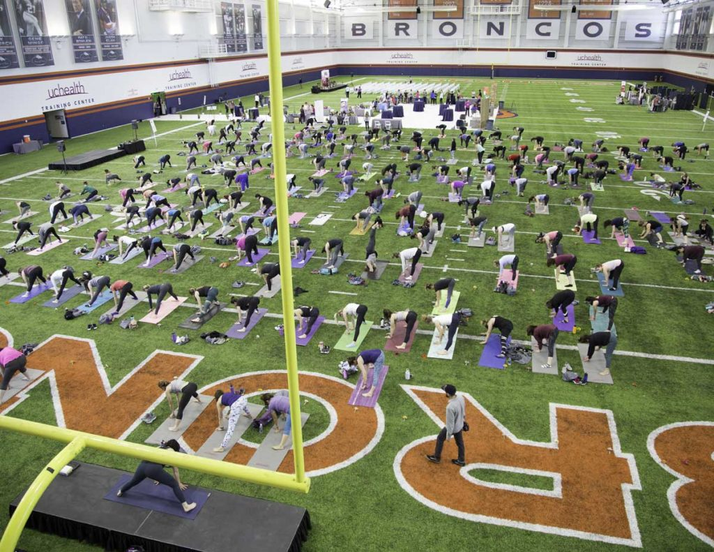 women with yoga mats cover the indoor training turf at the UCHealth Denver Broncos training center
