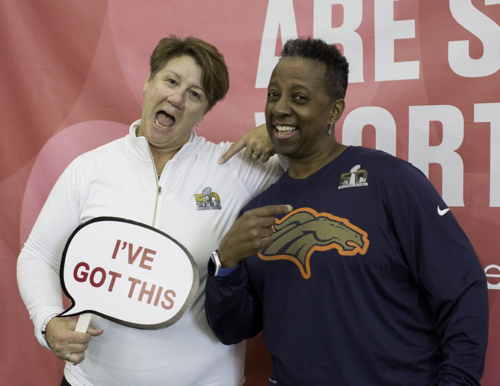 "Two women pose at a photo booth. One is holding a sign that says, ""I've got this."""