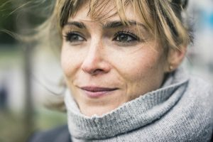 A middle-aged woman outside, wearing a turtlenext sweater.