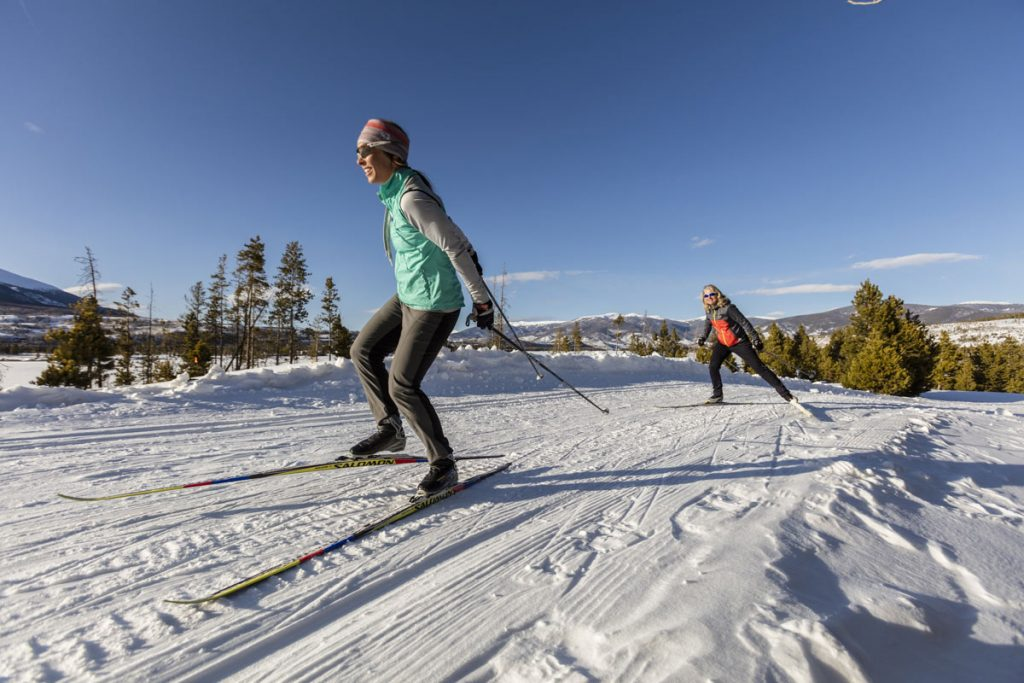 two skate skiers on cross-country skis at the Frisco Nordic Center