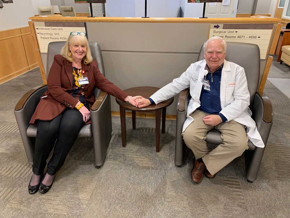 couple sits on chairs holding hands in the surgical unit waiting area