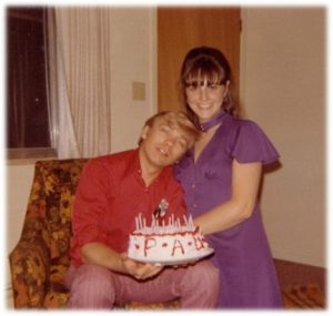 donna poses with paul, who is holding a birthday cake