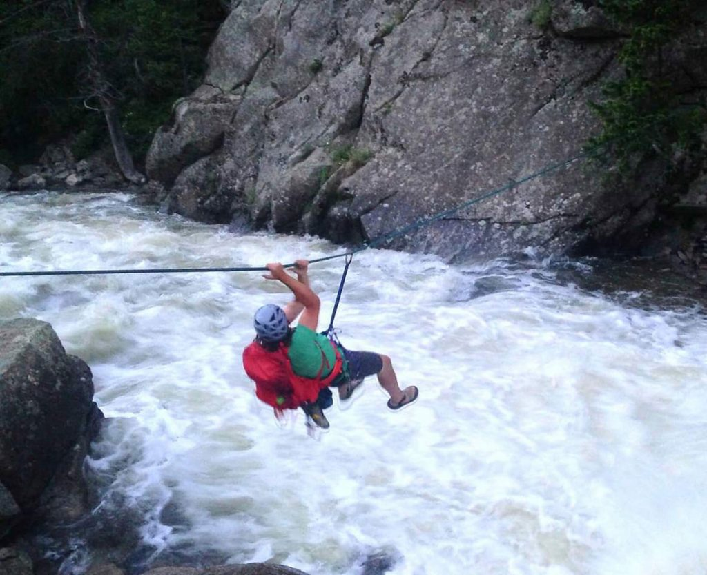 A man crosses a white water on a churning river. He's sliding on a rope to get across.
