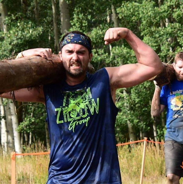 A strong guy carries a big log in a Tough Mudder compeition.